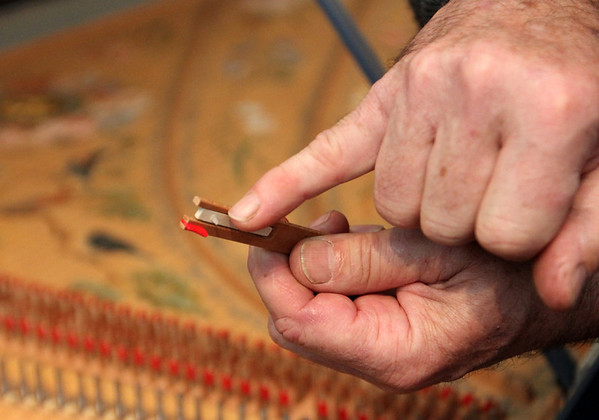ALLEGRA BOVERMAN/Staff photo. Gloucester Daily Times. Gloucester: Greg Bover holds a wooden jack with the tiny pinpoint-like plectrum, which plucks the harpsichord's strings.