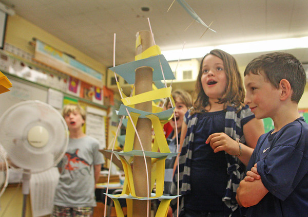 Jesse Poole/Gloucester Daily Times May 25, 2012— Third-graders Bonnie Gerhardt and Ethan Goldman watch as a fan blows the roof off of Ethan's model skyscraper at Essex Elementary School on Friday morning.