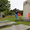 ALLEGRA BOVERMAN/Staff photo. Gloucester Daily Times. Gloucester: Gloucester Firefighter Tony Trupiano places a new flag at the Firefighters Memorial at the Cherry Hill Cemetery on Tuesday morning. Flags were placed at gravesites throughout the city's cemeteries on Tuesday in preparation for both Memorial Day, because many firefighters also were veterans, but also for the upcmoing Firefighters Memorial Service to be held at 8:45 a.m. on Sunday, June 10. A parade will step off from the Department of Public Works on Poplar Street and make its way to Cherry Hill Cemetery to the Firefighters Memorial. If it rains, the ceremony will be held at the fire department's headquarters.