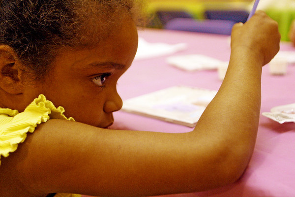 Kihanna Boutchie, 4, carefully adds the finishing touches to her painted tile, which will be added to a wall of painted tile at Pathway for Children on Wednesday afternoon. Jesse Poole/Gloucester Daily Times May 9, 2012