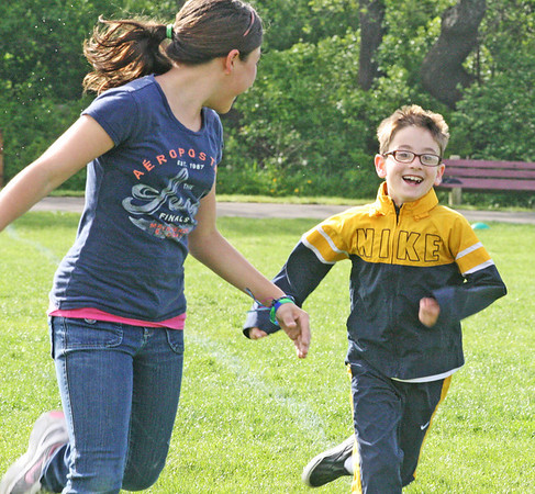 Jesse Poole/Gloucester Daily Times May 15, 2012 GLOUCESTER— Abby Engel, fifth grade, and Zack Champagne, second grade, race to the track during running club at Rockport Elementary School on Tuesday morning.