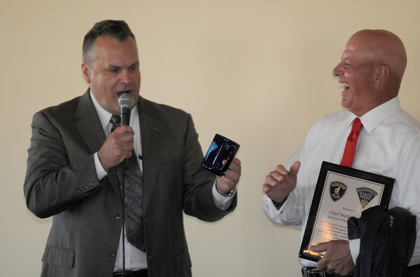 Gloucester:  Retiring Gloucester Interim Police Chief Michael Lane laughs as he recieves a coffee mug and a golf jacket from friend Scott White of the Mass State police at a recieption dinner for him at the Cruiseport in Gloucester Wednesday night. JIm Vaiknoras/staff photo