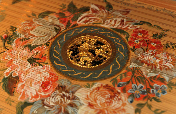 ALLEGRA BOVERMAN/Staff photo. Gloucester Daily Times. Gloucester: Detail of the harpsichord's spruce soundboard depicting some of France Fitch's and Greg Bover's favorite flora and fauna handpainted by Carole Bolsey. The center features each of the couple's last name initials.