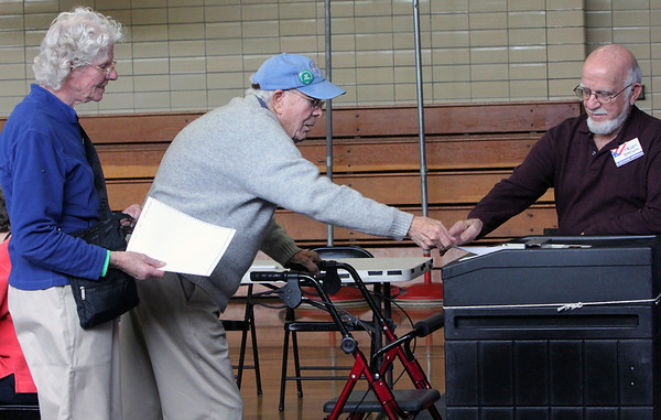 ALLEGRA BOVERMAN/Staff photo. Gloucester Daily Times. Manchester: Hilary and Al Creighton, left, vote during Manchester Election Day on Tuesday at Manchester Memorial Elementary School. Ted Brown, an election official, right, helps them.