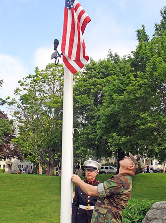 Jesse Poole/Gloucester Daily Times May 28, 2012 ESSEX— Raymond Greene, left, and David Oliver, both of Essex, lower the American flag to half mast on Monday morning at Memorial Park in Essex.