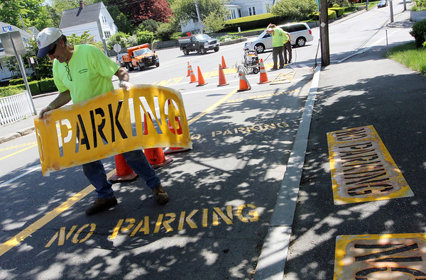 """ALLEGRA BOVERMAN/Staff photo. Gloucester Daily Times. Rockport: Bill Aspesi, Rockport highway foreman, lifts a stencil off a freshly painted """"no parking"""" road marking along Main Street on Thursday afternoon. New lettering and lines are being painted all over town and started on Thursday."""