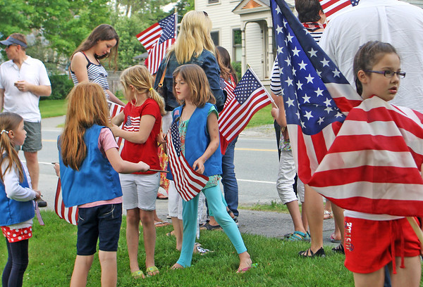 Jesse Poole/Gloucester Daily Times May 28, 2012 ESSEX— Faith Costello, 9, of Essex, wraps herself in a large American flag as she and the rest of the Brownie Girl Scout Troop wait for the Memorial Day ceremony to begin at Memorial Park in Essex on Monday morning.