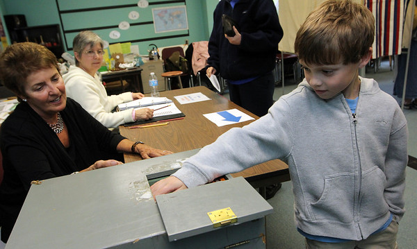ALLEGRA BOVERMAN/Staff photo. Gloucester Daily Times. Rockport: Colin Porter, 7, right, places a ballot filled out by his mother, Mary Porter, into <br /> the old fashioned hand-cranked Precinct Three at Rockport Elementary School on Tuesday. At about 3 p.m. there were more than 500 votes cast at that location. Liz Pszenny, left, and Andrea Ritchie, working at the polls, look on.