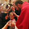Gloucester: At the Annual Crowning Feast of the Holy Spirit held at Our Lady of Good Voyage Parish on Sun., May 15, 2016. Bart and Mary Piscitello were honored this year with the Crown and they and their family were crowned first at the end of the Mass. Father Jim Achadinha, right, blesses Melissa Babine and her son Kayden, 1 1/2,  granddaughter and great-grandson of Mary and Bart. Mark Davis assists, background.<br /> Photo by Allegra Boverman