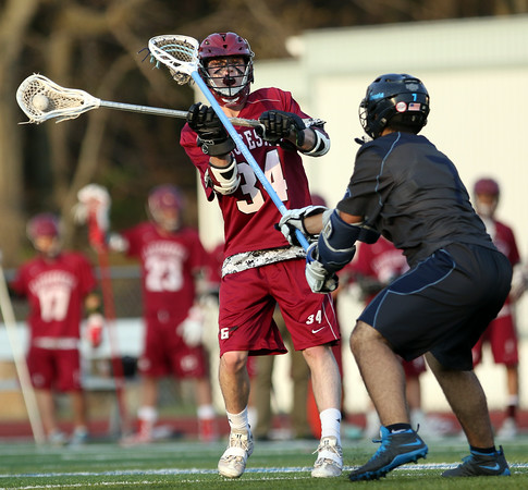 DAVID LE/Staff photo. Gloucester's Pat Goss fires a pass to a teammate behind the net against Peabody on Thursday evening. 5/12/16.
