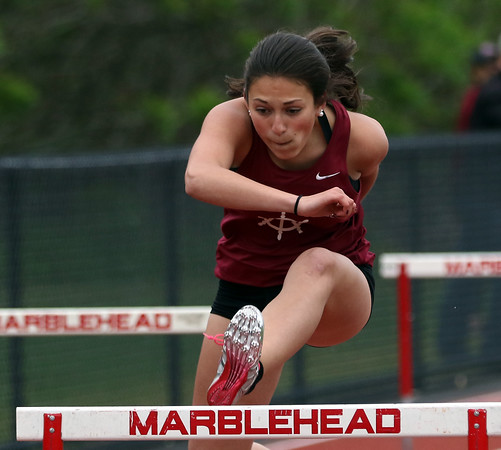 DAVID LE/Staff photo. Gloucester sophomore Kaitlin Marques leaps over the last hurdle and streaks towards the finish line to take first place in the 100 meter hurdles against Marblehead. 5/24/16.