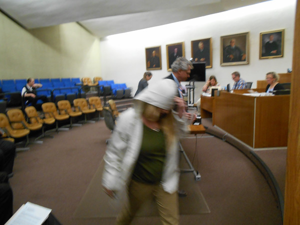 RAY LAMONT/Staff photo<br /> Gloucester artist Tina M. Greel, covering her head, leaves Gloucester District Court after her arraignment Tuesday on charges she threatened to blow up a Navy ship that was in port.