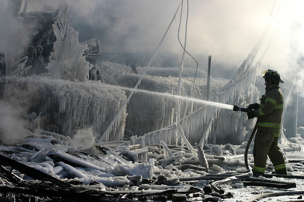 Gloucester: A firefighter hoses down the hot spots at the scene of a fire on Middle Street. Photo by Amy Sweeney Gloucester Daily Times. Saturday, December 15, 2007