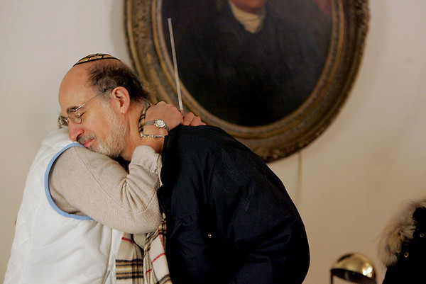 Gloucester:  Alan Feldman hugs Ruth Budelmann during a prayer service held for those who lost their temple in an eight alarm fire early Saturday morning.  Rabi Samuel Barth of Temple Ahavat Achim held the service at the Unitarian Universalist Church  on Middle Street.  <br /> Photo by Mary Muckenhoupt/Gloucester Daily Times. Saturday, December 15, 2007