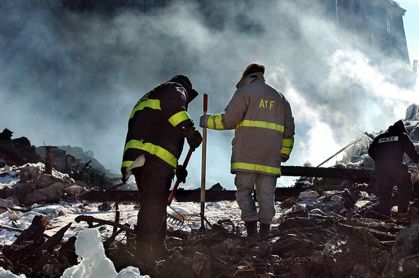 Gloucester: Investigators from the State Fire Marhall's office, left, and the Bureau of Alcohol, Tobacco, Firearms and Explosives, right, sift though the debris from the Lorraine Apartment building Tuesday morning. <br /> Photo by Mike Dean/Gloucester Daily Times Tuesday, December 18, 2007