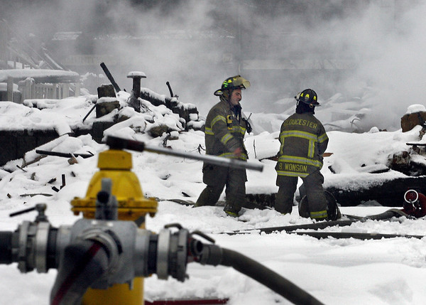 """Gloucester: Firefighter Bruce Wonson, right, and acting captain Phil Harvey work on laying a line at the site of the Middle Street fire Sunday afternoon. The fire department continued to douse the fire all day Sunday. """"There's still a lot of heat there,"""" said Harvey. """"We're trying to cool it down."""" Debris removal will begin Monday.<br /> Photo by Mike Dean/Gloucester Daily Times Sunday, December 16, 2007"""