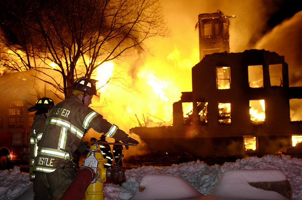 Gloucester: A firefighter works the hydrant at the massive fire on Middle Street. Temple Ahavat Achim was destroyed as well as a four-story apartment building.Photo by Jim Daly/Gloucester Daily Times Saturday, December 15, 2007