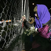 Gloucester:Amy Kaplan of Gloucester places a small white flower on the chain link fence that surrounds the rubble of Temple Ahavat Achim and the Lorraine Apartment Building. The Temple held a memorial service Thursday evening which started at the scene of the fire and ended at the Unitarian Universalist church. <br /> Photo by Deborah Hammond/Gloucester Daily Times Thursday, December 20, 2007