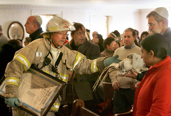 Gloucester:  Deputy Chief Phil Dench hands over some salvaged items that were not destroyed from the fire at Temple Ahavat Achim  during a prayer service held at the Unitarian Universalist Church on Middle Street Saturday morning.  Temple Ahavat Achim was destroyed in a massive fire early Saturday morning.  <br /> Photo by Mary Muckenhoupt/Gloucester Daily Times. Saturday, December 15, 2007