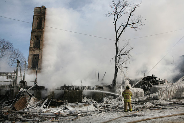 Gloucester: A firefighter works on the hot spots of the scene of an 8-alarm fire, which destroyed an apartment building and Temple Ahavat Achim. Photo by Amy Sweeney Gloucester Daily Times. Saturday, December 15, 2007