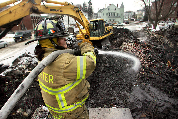 Gloucester: Gloucester firefighter Carol Blanchard works to put out hot spots on the still smoldering pile of rubble that was once Lorraine Apartments Wednesday afternoon.  Officials met yesterday and concluded that they do not know the cause of the fire. <br /> Photo by Mary Muckenhoupt/Gloucester Daily Times Wednesday, December 19, 2007