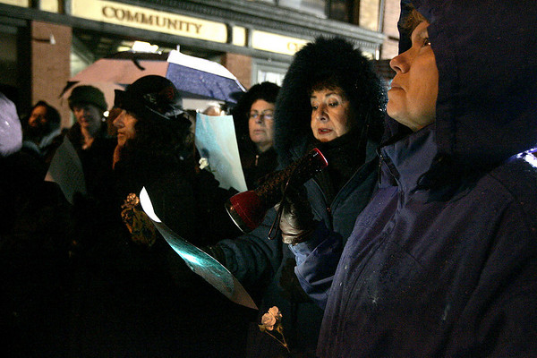 Gloucester:From left, Mimi Kantor, Robin Saipe, and Connie Zaitchek all of Gloucester sing songs in front of the rubble of Temple Ahavat Achim and the Lorraine Apartment Building on Middle Street during a memorial service Thursday evening. The Temple held the memorial service which started at the scene of the fire and ended at the Unitarian Universalist church. <br /> Photo by Deborah Hammond/Gloucester Daily Times Thursday, December 20, 2007