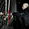 Gloucester:Owen Kantor of Gloucester places a small white flower on the chain link fence that surrounds the rubble of Temple Ahavat Achim and the Lorraine Apartment Building. The Temple held a memorial service Thursday evening which started at the scene of the fire and ended at the Unitarian Universalist church. <br /> Photo by Deborah Hammond/Gloucester Daily Times Thursday, December 20, 2007