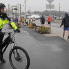 DIMITRA LAVRAKAS/Staff photo<br /> Essex police Officer Daniel J. Bruce prepares to accompany gathering racers on the police department's new electric bike for the start of the Essex Lion's Turkey Trot on the Main Street Causeway on Sunday.