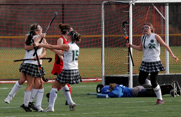 North Andover: Manchester Essex's Kyle Marsh (hidden) and Lizzy Ball (15) hug Amelia Burke as teammate Katie Gavin runs in to celebrate Burke's goal against Watertown in the Division II North Field Hockey Championship at North Andover High School yesterday afternoon. Photo by Kate Glass/Gloucester Daily Times Sunday, November 15, 2009