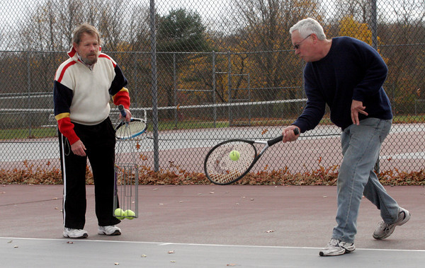 Rockport: Timothy Ewald helps Kevin Burke work on his forehand at the tennis courts behind Rockport Elementary School yesterday afternoon. Burke recently started playing tennis because he thought it would be a good way to get excercise. Photo by Kate Glass/Gloucester Daily Times Wednesday, November 11, 2009