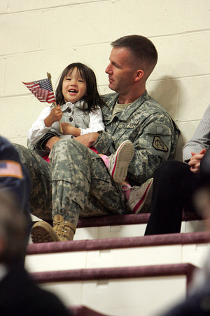 Gloucester: Dean Klopotski, memeber of the United Stetes Army, sits with his daughter Rosanna, 4, at the Veteran's Day Cemenony at Gloucester High School Wednesday morning. Mary Muckenhoupt/Gloucester Daily Times