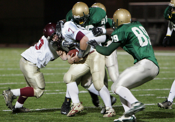 Gloucester: Gloucester's Brett Cahil gets sacked by Lynn Classical defenders including Chevere Archer and John Grocki, left, duing the first half of the football game at Manning Field in Lynn Friday night. Mary Muckenhoupt/Gloucester Daily Times