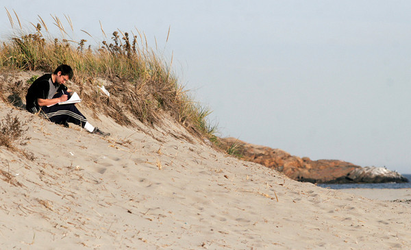 Gloucester: Travis Derocher of Gloucester finds a quiet spot on a sand dune for writing at Good Harbor Beach yesterday afternoon. Photo by Kate Glass/Gloucester Daily Times Monday, November 9, 2009