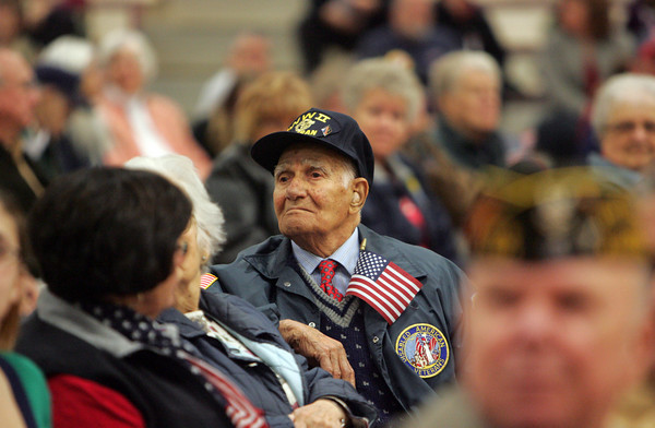 Gloucester: World War II veteran Alfred Piscatello listens to the Plum Cove School singers during the Veteran's Day Ceremony at Gloucester High School Wednesday morning. Piscatello served as a medic with the army unit that was attached to the 1st Marine Division at Guadalcanal in the South Pacific. Mary Muckenhoupt/Gloucester Daily Times