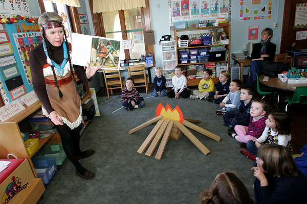 "Gloucester: Pre-kindergarten teacher TamiÊCronin, dressed as Pocahontas, reads a story called ""The Rough faced Girl"" to her students and to friends and family at the Eastern Point Day School Thursday morning. After the story the kids got to make their own Indian headdresses and have a snack of corn cakes and apple cider. Mary Muckenhoupt/Gloucester Daily Times"