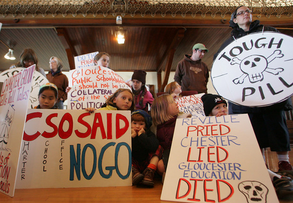 Gloucester: Children and parents hold signs in protest at a hearing of the State Board of Elementary and Secondary Education over it's approlval of the Gloucester Charter School at City Hall Saturday afternoon. Many fear the new charter school wil draw too much money away from the other schools in the district. Mary Muckenhoupt/Gloucester Daily Times