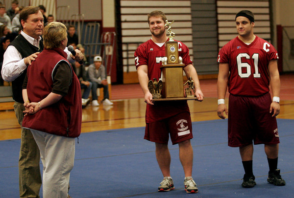 Gloucester: Assistant Football Coach Tom Walsh asks Athletic Director Kim Patience what she thinks the score of the Thanksgiving game will be as captains Brett Cahill and Gus Margiotta show off the Thanksgiving Trophy during a pep rally in the Benjamin A. Smith Field House yesterday afternoon. Photo by Kate Glass/Gloucester Daily Times Wednesday, November 25, 2009