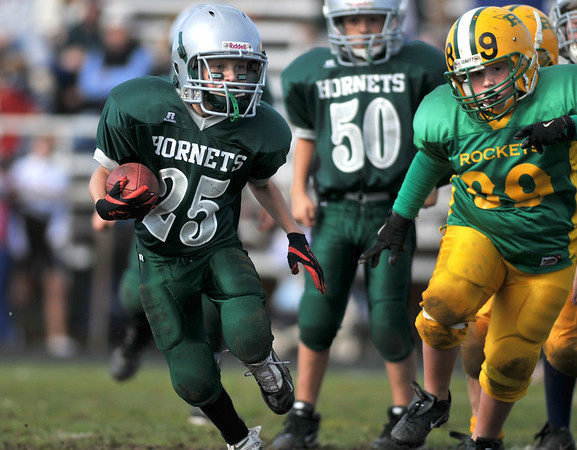 Gloucester: Hornet's C-Team's Jack Julian carries the ball up feild as Rocket's Ryan Sanfilippo gives chase in Sunday's Pee Wee Football games  at Newell Stadium. Desi Smith Photo/Gloucester Daily Times. November 1,2009.
