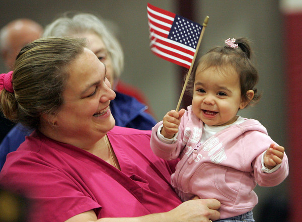 Gloucester: Catherine Wood smiles as her daughter Maria Isabel Sierra, 13 months, waves an American flag at the Veteran's Day Ceremony at Gloucester Daily Times Wednesday morning. Mary Muckenhoupt/Gloucester Daily Times