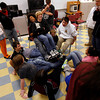 Gloucester: Phil Curcuru laughs as he sits in Darrell Marsh's lap while they and other students in the Healthy Gloucester Collaborative program try to fit everyone's feet into a small circle during a Project Adventure workshop on Thursday. The collaborative contains students from Gloucester Stage's Youth Acting Workshop, SADD, Chill Zone, YMCA, and Interact, and focuses on youth leadership. Photo by Kate Glass/Gloucester Daily Times Thursday, November 19, 2009