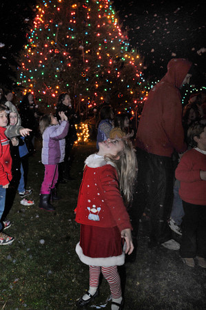 Gloucester: Lily Marshall 6, catches snow flakes made by a machine on her head as others use their hands at Kent Circle after the tree lighting.Desi Smith Photo/Gloucester Daily Times. November 29,2009.