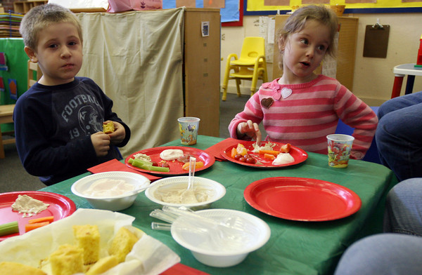 Gloucester: Anthony Favazza, and Cassandra Napoli, both 3, share a table during Gloucester Preschool's Thanksgiving dinner at the Fuller School yesterday. The classes each performed for their families and then ate food the kids helped prepare. Photo by Kate Glass/Gloucester Daily Times Tuesday, November 24, 2009