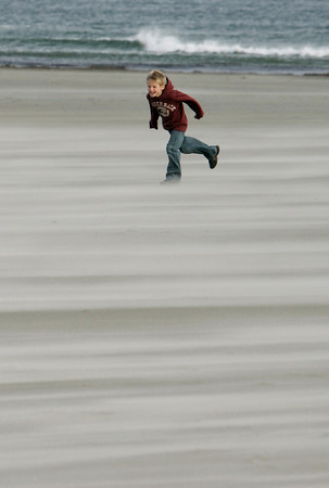 Gloucester: Nicholas Hovis, 8, of Gloucester tries to run into the wind at Good Harbor Beach Saturday afternoon.  Nicholas who was at the beach with his family and dog, Rags, didn't stay too long because it was so windy. Mary Muckenhoupt/Gloucester Daily Times