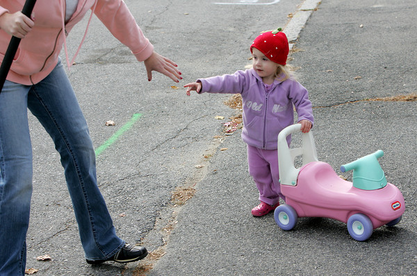 Gloucester: Elizabeth McCoy, 2, of Gloucester stops pushing her car to hold her mother Heather's hand as Elizabeth plays in the sidewalk while her mother tries to get some yard work done Thursday afternoon. Mary Muckenhoupt/Gloucester Daily Times