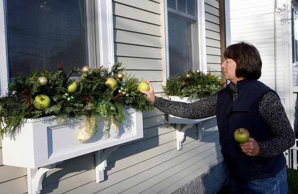 "Gloucester: Karen Maley of Blue Gate Gardens in Rockport decorates the window boxes at 4 Leonard Street in Annisquam. The home is one of several featured in the ""Home for the Holidays"" tour on Saturday. Photo by Kate Glass/Gloucester Daily Times Tuesday, November 17, 2009"