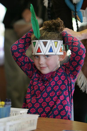 Gloucester: Maggie Sperry ties on the Indian headdress she made with her pre-kindergarten class at the Eastern Point Day School Thursday morning.  The students along with friends and family listened to Pocahontas read them a story before they got to make their craft and enjoy corn bread and apple cider. Mary Muckenhoupt/Gloucester Daily Times