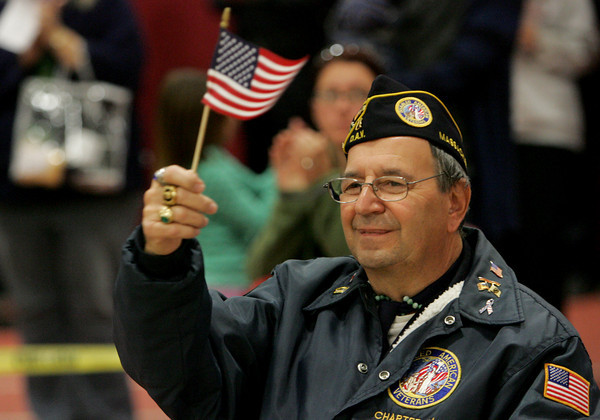 Gloucester: Samuel Calomo waves an American Flag as the men and women of the military are honored at the Veterans Day Ceremony at Gloucester High School Wednesday afternoon.  Calomo was a combat medic in the U.S. Army during the Vietnam War. Mary Muckenhoupt/Gloucester Daily Times
