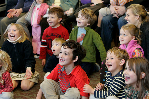 Manchester: Ryan Meehan, 7, front, center, and his brother Cole, 4, right, laugh along with the crowd of children at Henry the Juggler who performed at Manchester Public Library Saturday morning.  After Henry perofrmed a variety of juggling trick he invited the kids to come up and learn the basics of juggling. Mary Muckenhoupt/Gloucestr Daily Times
