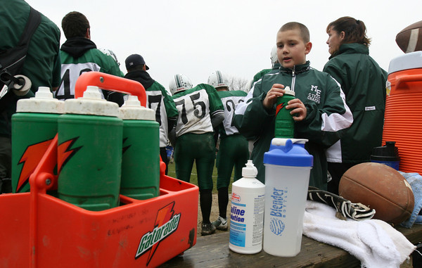 Cosmo Pallazola refills water bottles for the Manchester Essex football team during their game against Georgetown on Thanksgiving day. Photo by Kate Glass/Gloucester Daily Times