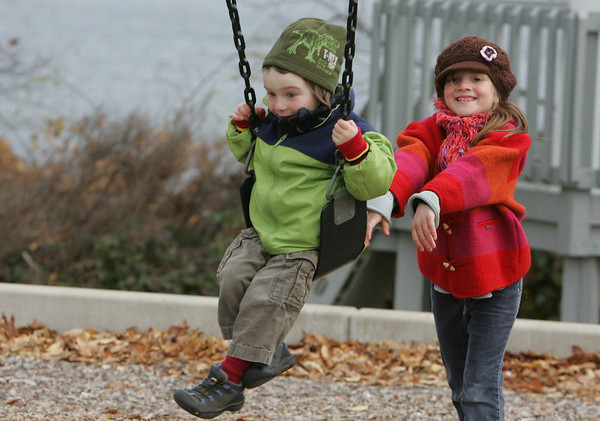 Gloucester: Madelyne Dixon, 7, of Gloucester pushes her brother Simon, 4, while playing at Stage Fort Park Wednesday.  Simon hasn't quite figured out how to keep himself swinging so Madelyne kept jumping off her swing to push her little brother. Mary Muckenhoupt/Gloucester Daily Times